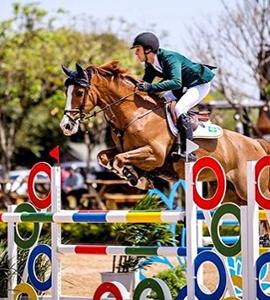 Pedro com seu cavalo saltando um obstáculo bem colorido a uma altura de 1,40m.
